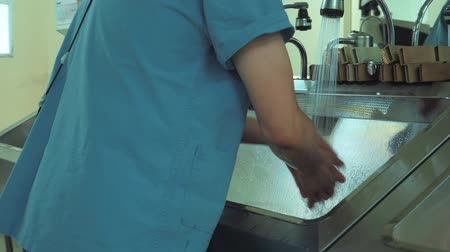 higiênico : Doctor surgeon in robe washes hands in washbasin before surgery