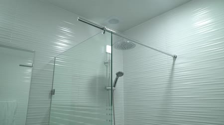tartó : Room with shower booth made of glass with hand-held adhesive hanging on the wall Stock mozgókép