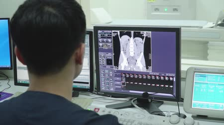 tomography : The doctor watches the results of MRI examinations of the patient on the monitor of the computer, on which the internal organs of the person are shown