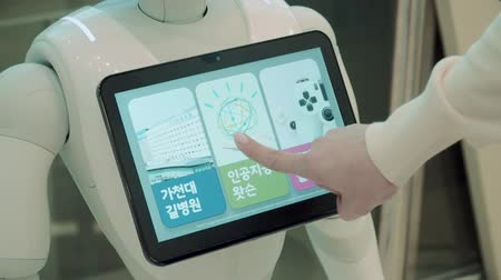 bot : Robot assistant of white color with monitor in chest on the screen of which is pressed by hand