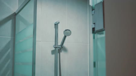 titular : Room with shower booth made of glass with hand-held adhesive hanging on the wall Stock Footage