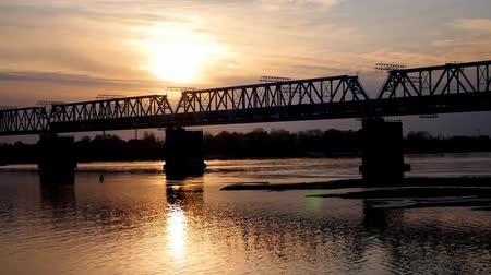 distância : train across the river at sunset