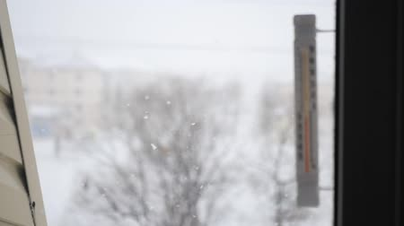 gravado : thermometer on the window with the focus on the movement of snowflakes on the street