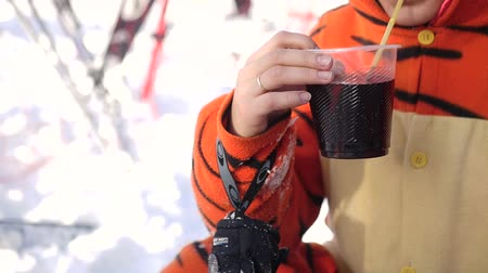 saman : young beautiful girl in costume tigers, drinking hot mulled wine from a plastic cup on a cafe in the open winter Stok Video