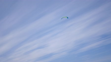 avançar : kitesurfing soaring in the blue sky with white clouds light