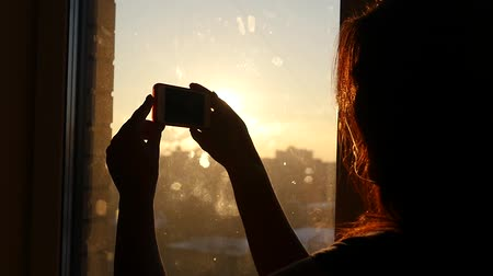 magány : young beautiful girl drives a finger on the phone near a window at sunset, slow motion, HD