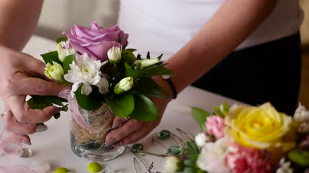 florista : florist girl collects a nice little bouquet of roses and other flowers in a small vase Stock Footage
