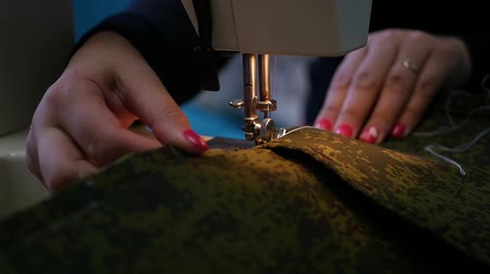 parecer : deushka with beautiful varnish on the nails on the sewing machine sews two dense fabric khaki, slow motion, HD, 1920x1080.