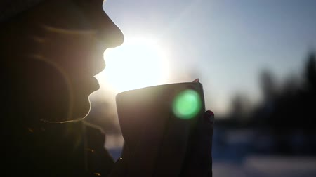 наслаждаясь : A young girl enjoying a delicious hot coffee standing on the street on a background of a beautiful winter setting sun, blowing into the cup. The effect of reflection rays from the lens. 1920x1080