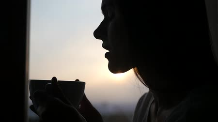 fresh coffee : An attractive girl is enjoying coffee on the background of a spring sunset outside the window, with the rays of the sun and the effect of the lens. 1920x1080. SLOW MOTION. HD,