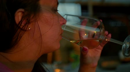 eleganckie : Girl sitting in a cafe drinking white wine from a glass, close-up. HD, 1920x1080. slow motion. Wideo
