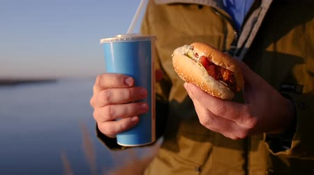 нездоровое питание : A hungry man holds a delicious hamburger and a glass of soda. slow motion, 1920x1080, full hd