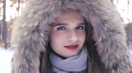 maska : A beautiful girl with a red lipstick in a hood with fur stands in a forest in the winter and turns away from the camera. HD, 1920x1080, slow motion Wideo