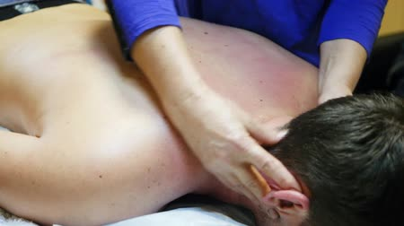 A woman massages a guys back and neck. 4k Stok Video