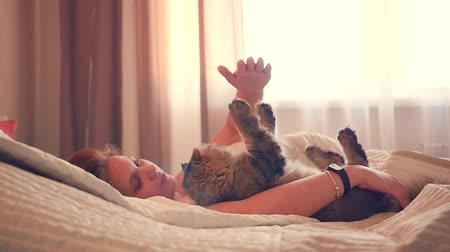 A young girl lies on her back on the bed with a cat and plays. HD,