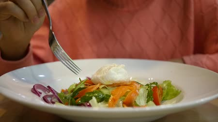 Girl eating salad with vegetables and red fish from a big plate in a cafe. HD, Stok Video