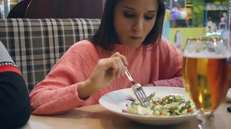 The girl is sitting in a cafe and eating a delicious salad with red fish and drinking it with beer. HD, Stok Video