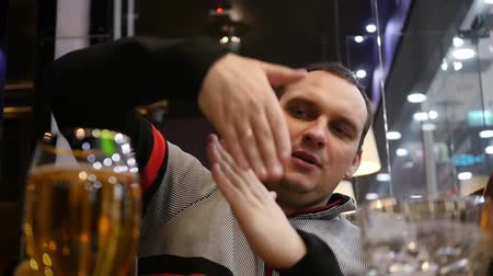 A young man is sitting in a cafe, drinking beer talking to friends, telling, showing gestures in his arms. HD,