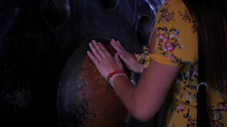 emit : A girl with long hair laid her hands on the holy gong in the temple. HD,
