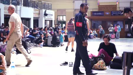 01302018 Banking, Thailand. A policeman at the station will excuse tourists from the floor in the center of the station, on benches. 4k, 3840x2160. HD Stok Video
