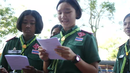 01302018 Banking, Thailand. Girls scouts in green uniforms hold a survey in the street, ask questions, passers-by, read from a leaflet. 4k, 3840x2160. HD