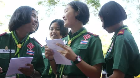 01302018 Banking, Thailand. Girls scouts in green uniforms hold a survey on the street, ask questions, passers-by, read from a leaf, feel shy and laugh. 4k, 3840x2160. HD