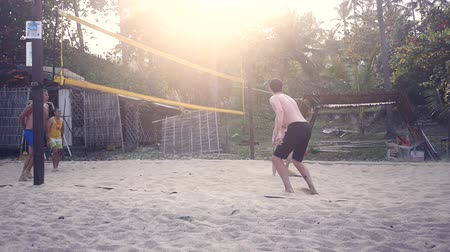 01.02.2018, Thailand, the island of Samui. Men and woman play beach volleyball at sunset. Slow Motion. HD, 1920x1080.