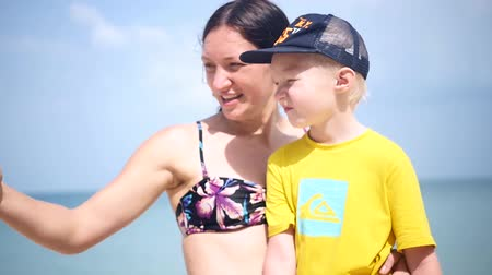 13.02. 2018 Taylan, Samui Island, Ban Tai beach. Mom and son do selfie on the beach, and she kisses her son on the cheek. slow motion. 1920x1080. full hd