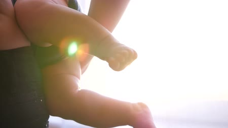 baby chubby : Pleasant childrens legs with folds against the window and sunset on the hands of my mother. HD, 1920x1080. slow motion.