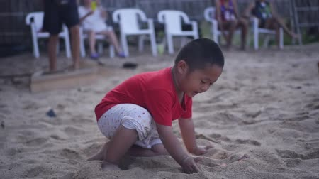 16022018 Thailand, Koh Samui, Chaweng Noi beach. The kid is playing on the beach in the sand near the volleyball court. HD, 1920x1080. slow motion
