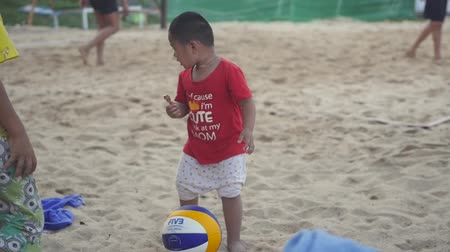 16022018 Thailand, Koh Samui, Chaweng Noi beach. A small funny boy stands on the beach at the volleyball court, takes the ball, helps and carries it to the players. HD, 1920x1080. slow motion