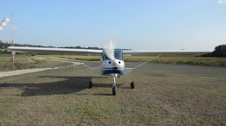 aerodrome : ROMA, ITALY - AUGUST 2018: The pilot on a light-engine aircraft Tecnam landed on a ground aerodrome and turns off the engine Stock Footage