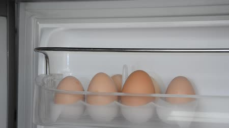 mrazák : A man takes an egg in the refrigerator