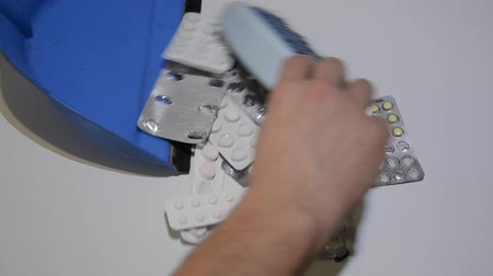 curativo : A man cleans pills and drugs with a scoop and brush in the trash Vídeos