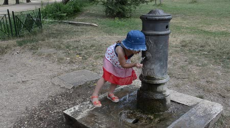 encanador : Girl drinking water from the drinking fountain