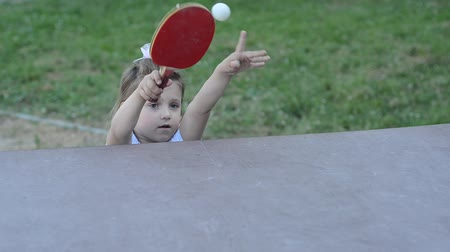 teniszütő : Little charming happy girl child plays table tennis Stock mozgókép