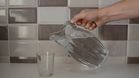 sürahi : A man pours pure water from a glass decanter into a glass cup Stok Video