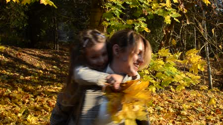 Young charming mother whirls holding her baby daughter in her arms among yellow fallen maple leaves, happy family
