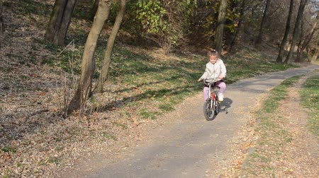 Little girl child learns to ride a bike in the autumn park Stock mozgókép