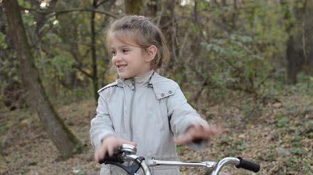 Little girl child shows heart and love hands on bicycle in autumn park
