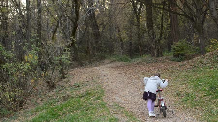 Little girl child taking a bicycle uphill in autumn park