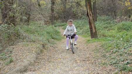 Little happy girl child rides a bicycle in the autumn forest Stock mozgókép
