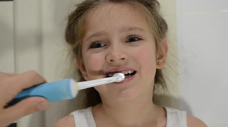 mosás : Girl child brushes her teeth with an electric toothbrush Stock mozgókép