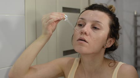 Young beautiful girl applies cosmetic therapeutic serum on her face with a pipette in the bathroom