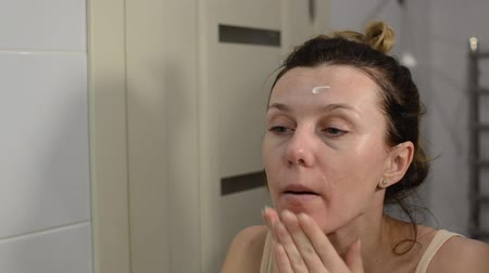 Young beautiful girl is applying face cream in the bathroom Stock Footage