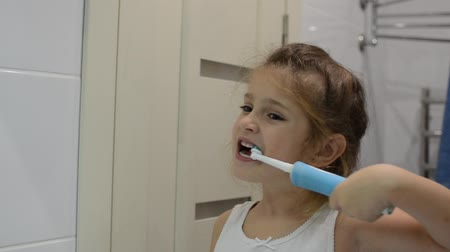 Girl child brushes her teeth with an electric toothbrush Stock mozgókép