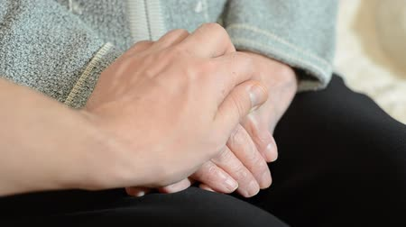 Son hugs the wrinkled hands of an old mother