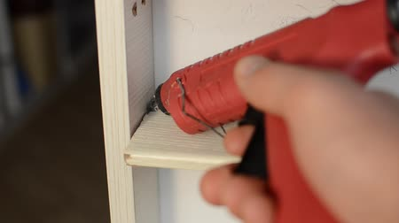 склеивание : The master repairs wooden shelves with hot glue with a plastic gun Стоковые видеозаписи