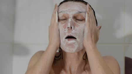 arcszín : Young charming sexy girl makes a white scrub mask on her face in the bathroom