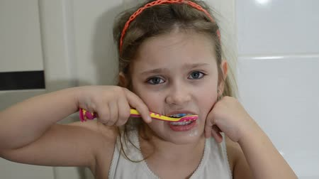 creme dental : Little charming baby girl brushing her teeth in the bathroom Stock Footage
